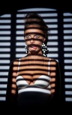 Woman in shadow of binds roller posing