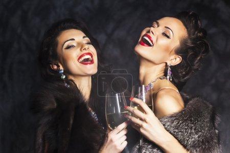 Photo pour Jeunes femmes heureuses de la mode célébrant l'événement. Toasts et félicitations - image libre de droit