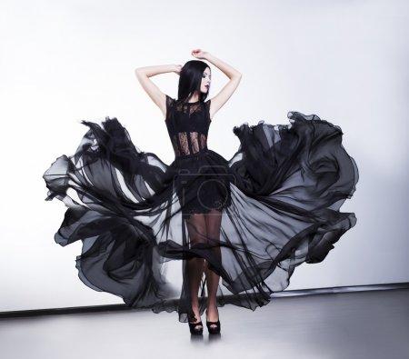 Photo pour Fantaisie. femme sexy à la mode en flottant noir robe moderne - image libre de droit