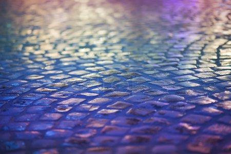 Cobble Stone Pavement - Reflexion in Urban Night. Wet Blue Sidewalk