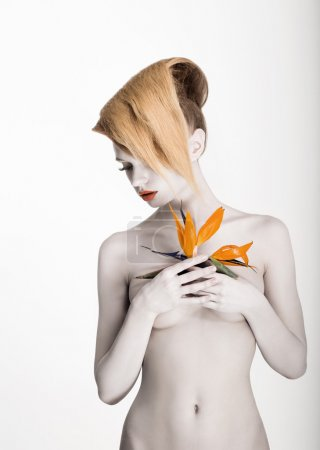White Body Art. Daydreaming Naked Woman holding Fresh Flower. Exotic Hairstyle