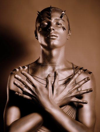 Colorear. Bodyart. Cuerpo de hombre pintado de bronce en la sombra. Gracia