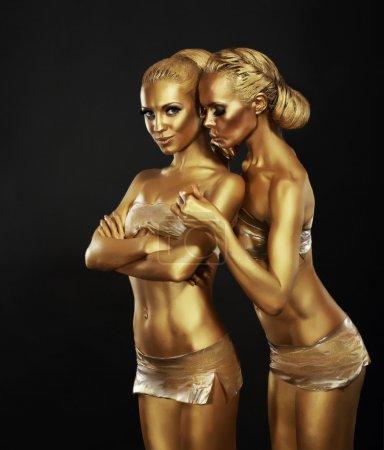 Bodyart. Girlfriends with Golden Makeup in Embrace. Art Deco