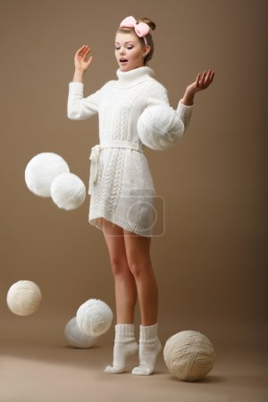 Falling Skeins. Surprised Woman in Woolen Knitted Jersey with White Balls of Yarn