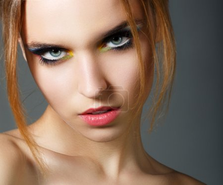 Magnetism. Character. Face of Young Red Hair Beauty with Colorful Eye Makeup
