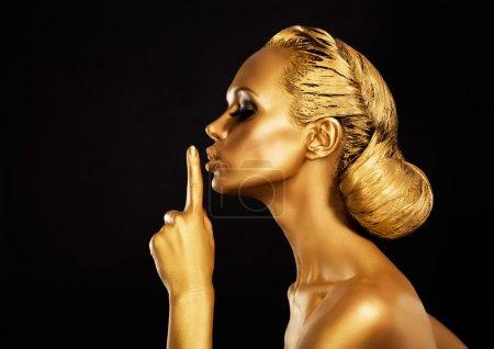 Secrecy. Bodyart. Golden Woman showing Silence Sign. Hush!