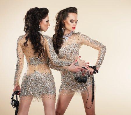 Soiree. Two Elegant Shapely Women in Grey Dresses