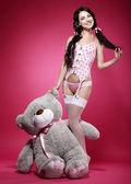 Compleanno. giocosa giovane donna seducente, tenendo il suo dono - teddy bear
