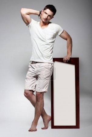 Elegant Young Man in White Cotton Clothes with Board Standing