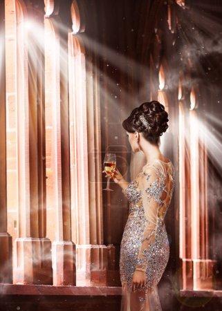 Photo pour Du luxe. Jeune femme en robe de soirée avec verre de champagne debout à la fenêtre au soleil - image libre de droit