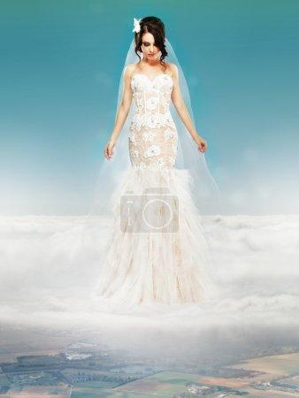 Braut im weißen Hochzeitskleid steht auf einer Wolke und blickt zu Boden