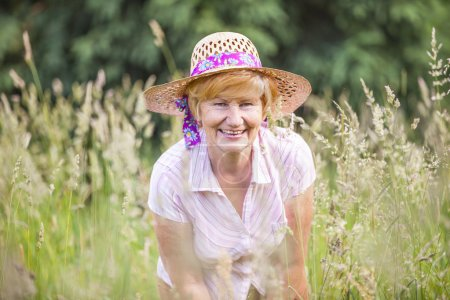 Photo for Positivity. Happy Senior Peasant Woman in Meadow smiling. Mature Friendly Lady in Bonnet - Royalty Free Image