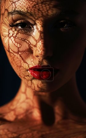 Photo for Reflection. Woman in Shadows with Reflection of Openwork Lace on her Face - Royalty Free Image