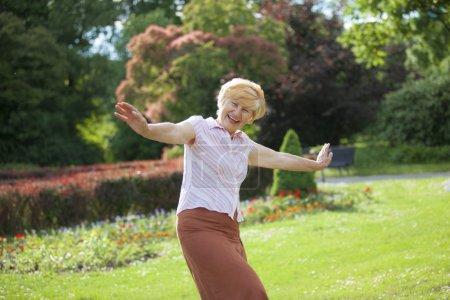 Photo pour La gaieté. Délicieux ludique mature femme avec les bras tendus rire à l'extérieur - image libre de droit