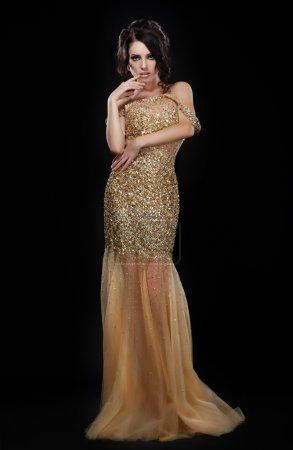 Foto de Fiesta formal. modelo glamorosa moda elegante vestido dorado sobre negro - Imagen libre de derechos