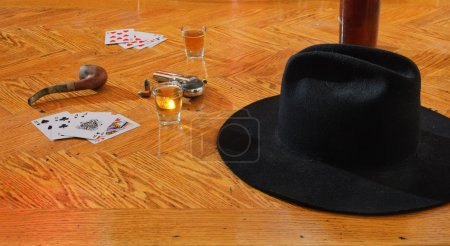 Whiskey, cards and gun and black hat on a floor
