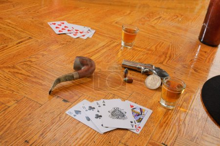 Whiskey, cards and gun on a floor