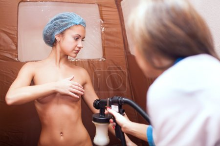 Young attractive brunette girl on the tanning process