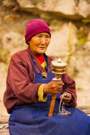 Tibetan Woman Pilgrim Praying Spinning Mani Wheel
