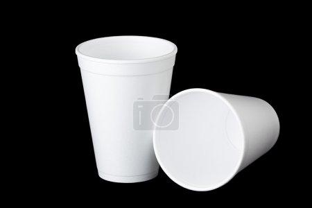 Photo pour Deux gobelets en polystyrène vides sur fond noir. une place est à l'endroit et la deuxième coupe pose à côté de la première. - image libre de droit