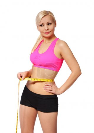 Fitness girl with measure tape. beautiful blonde young woman measuring her waist isolated on white background