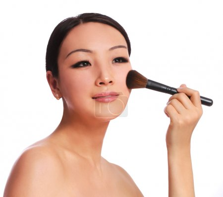 Woman with makeup brush. beautiful Asian brunette applying blush on her cheek, isolated on white