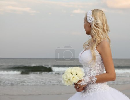 Blonde bride walking on the the beach. beautiful young woman in wedding dress looking on the ocean