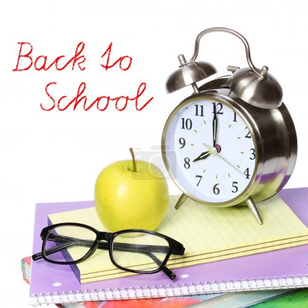 Back to school concept. An apple, alarm clock and glasses on pile of books isolated on white background