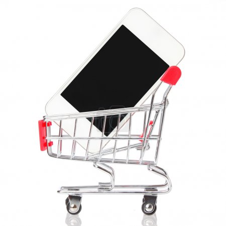 Cell phone in shopping cart isolated on white. Mobile phone in trolley. Concept