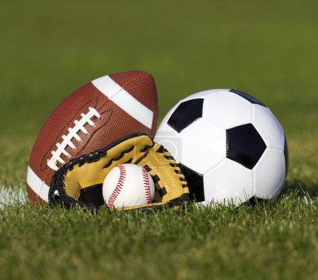 Sports balls on the field with yard line. Soccer ball, American football and Baseball in yellow glove on green grass. Outdoors