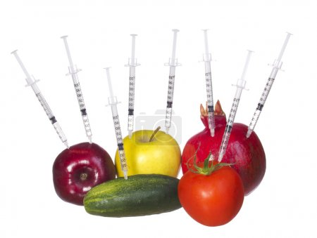 GMO food concept. Genetically modified fruit and vegetables with syringes isolated on white background. Genetic injections
