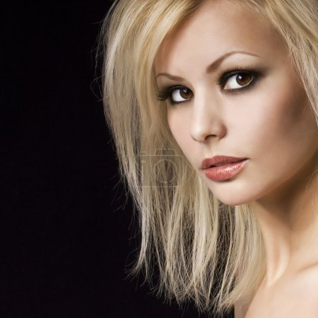 Fashion portrait. Beautiful blonde woman with professional makeup, over black background. Vogue style model