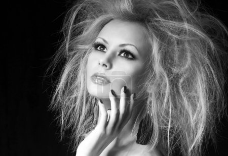 Fashion blonde girl. Beautiful woman with professional makeup and humidity hair style, over black background. Vogue model. Black and white