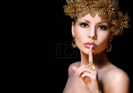 Fashion Girl with Gold Jewelries over black background. Beauty