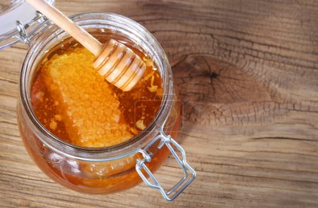 Jar of honey with honeycomb and dipper on wooden background