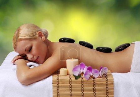 Photo pour Massage aux pierres Spa. Belle femme blonde Obtenir des pierres chaudes Salon. Soins de beauté . - image libre de droit