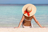 Sexy girl on tropical beach. Vacation. Woman in Sun Hat tanning