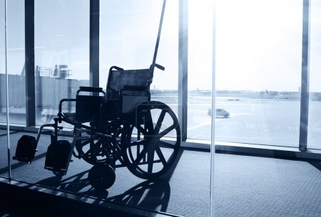 Wheelchair Service in Airport Terminal. Window View with Sunligh