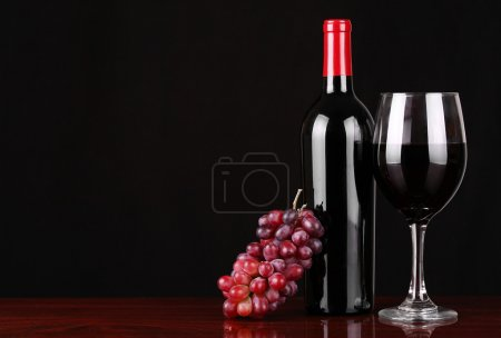 Wine Bottle and Glass of Red Wine with Fresh Grapes over black