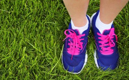 Sport Footwear on Female Feet on Green Grass. Closeup Running Sh
