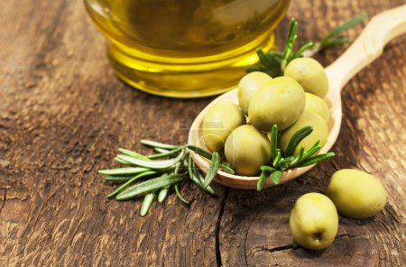 Photo pour Olives au romarin et huile d'olive sur un fond de bois - image libre de droit