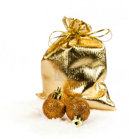 golden gift bag and christmas balls in the snow