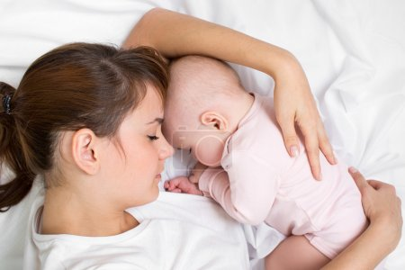 Young mother embracing her sleeping baby