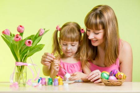 Mother and daughter kid painting easter eggs