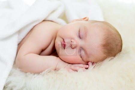 Newborn baby girl sleeping on fur bed