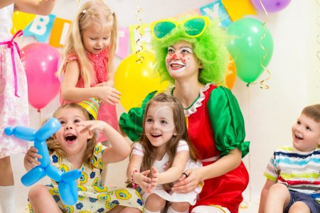 jolly children with clown on birthday party