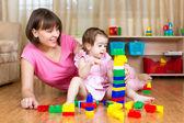 Matka a její dcera hrát s hračkami na domácí interiér