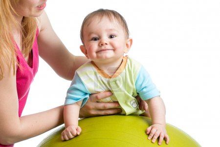 Mom doing gymnastics to her son baby on fitness ball