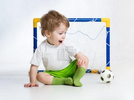 kid football player looking at soccer ball