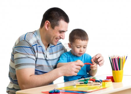 Happy father and child boy play clay together